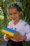 Flickan i broderi bokar med den ukrainska flaggan för färg Royaltyfri Bild