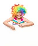 Flickan i clown rymmer det tomma banret Arkivbild