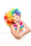 Flickan i clown rymmer det tomma banret Royaltyfri Fotografi