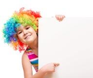 Flickan i clown rymmer det tomma banret Royaltyfri Foto