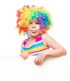 Flickan i clown rymmer det tomma banret Arkivfoto