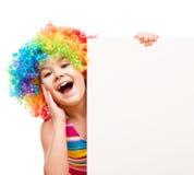 Flickan i clown rymmer det tomma banret Arkivbilder