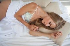 Flickan i damunderkläder sover i säng i morgonen, vit Arkivbilder