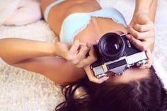 Flickan i damunderkläder tar bilder Arkivbilder