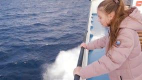 Flickan i de rosa omslagsflötena på fartyget Turisten går på vattnet, havet, floden, ung tonåring med långt blont arkivfilmer