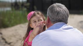 Flickan i defocusen kör till hennes farfar som kramar honom Hon ser i ramen och leendena 4K l?ngsam mo stock video