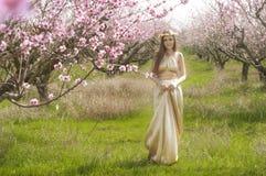 Flickan i den blommiga trädgården Arkivbild