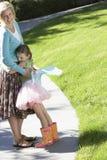 Flickan i den felika dräkten som omfamnar modern på, parkerar Arkivbilder