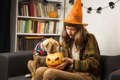 Flickan i den halloween hatten sitter med den nyfikna hunden som klibbar dess näsa Arkivfoto