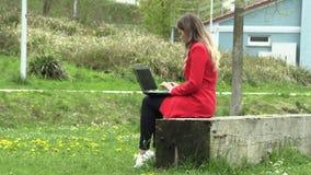 Flickan i den röda klänningen arbetar på gatan med en bärbar dator lager videofilmer