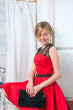 Flickan i den röda klänningen sitter på en resväska framme av en fol Royaltyfri Bild