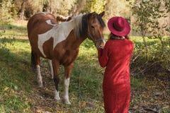 Flickan i den röda koftan med hästen Fotografering för Bildbyråer