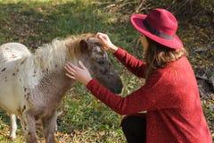 Flickan i den röda koftan med hästen Royaltyfri Fotografi