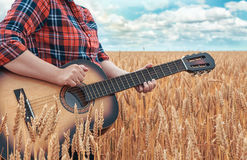 Flickan i den röda skjortan i vetefält spelar den akustiska gitarren Härlig natur på den ljusa soliga sommardagen Arkivbild