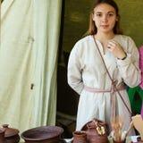 Flickan i den ryska nationella klänningen som står bak räknaren av en krukmakeri, shoppar royaltyfri foto