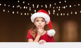 Flickan i den santa hatten med brädedanande hyssjar gest Royaltyfria Foton