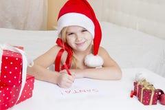 Flickan i den santa hatten, skrivar ett brev till jultomten Arkivfoton