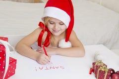 Flickan i den santa hatten, skrivar ett brev till jultomten Fotografering för Bildbyråer