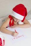 Flickan i den santa hatten, skrivar ett brev till jultomten Arkivfoto
