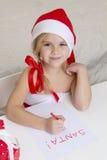 Flickan i den santa hatten, skrivar ett brev till jultomten Royaltyfri Fotografi