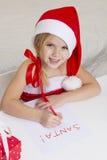Flickan i den santa hatten, skrivar ett brev till jultomten Royaltyfri Bild
