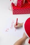Flickan i den santa hatten, skrivar ett brev till jultomten Arkivbilder