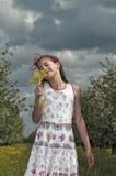 Flickan i den sura körsbärsröda fruktträdgården tycker om blommor Arkivbilder