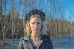 Flickan i den svarta kransen av blommor som ser kameran Fotografering för Bildbyråer