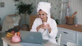 Flickan i den vita badrocken, med handduken på huvudet har video pratstund på bärbara datorn, ultrarapid lager videofilmer