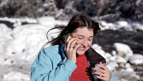 Flickan i det blåa omslaget på en solig vinterdag går sjön i skogen och talar vid telefonen arkivfilmer