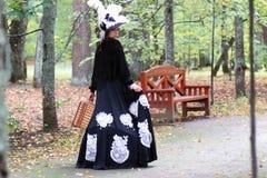 Flickan i det 18th århundradet för den retro klänningen med valise parkerar in Royaltyfri Bild