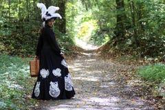 Flickan i det 18th århundradet för den retro klänningen med valise parkerar in Royaltyfria Foton