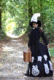 Flickan i det 18th århundradet för den retro klänningen med valise parkerar in Royaltyfri Foto