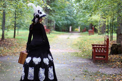 Flickan i det 18th århundradet för den retro klänningen med valise parkerar in Royaltyfria Bilder