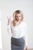 Flickan i en affärsdräkt visar tecken händer royaltyfri foto