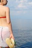 Flickan i en baddräkt mot havet Arkivfoto