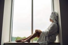 Flickan i en badrock och en handduk på huvudet sitter på fönstret Arkivfoto