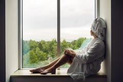 Flickan i en badrock och en handduk på huvudet sitter på fönstret Royaltyfri Foto