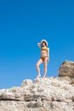 Flickan i en bikini, en hatt och en solglasögon som solbadar på bakgrunden av vit, vaggar Royaltyfri Foto
