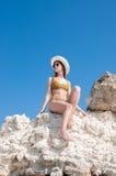 Flickan i en bikini, en hatt och en solglasögon som solbadar på bakgrunden av vit, vaggar Royaltyfria Bilder