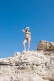 Flickan i en bikini, en hatt och en solglasögon som solbadar på bakgrunden av vit, vaggar Arkivfoto