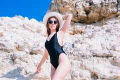 Flickan i en bikini, en hatt och en solglasögon som solbadar på bakgrunden av vit, vaggar Arkivbild