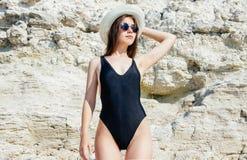 Flickan i en bikini, en hatt och en solglasögon som solbadar på bakgrunden av vit, vaggar Arkivfoton