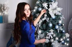 Flickan i en blå klänning dekorerar en julgran fotografering för bildbyråer