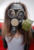 Flickan i en gasmask. Arkivfoton