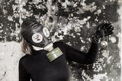 Flickan i en gasmask Hotet av ekologi arkivbilder