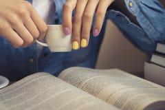 Flickan i en grov bomullstvillskjorta sitter på tabellen och läsningen en bok Arkivfoton