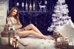 Flickan i en guld- klänning bredvid trädet Royaltyfria Bilder