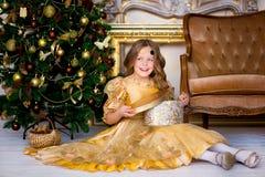 Flickan i en guld- klänning på jul Royaltyfri Bild