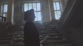 Flickan i en hatt går i en förstörd byggnad stock video